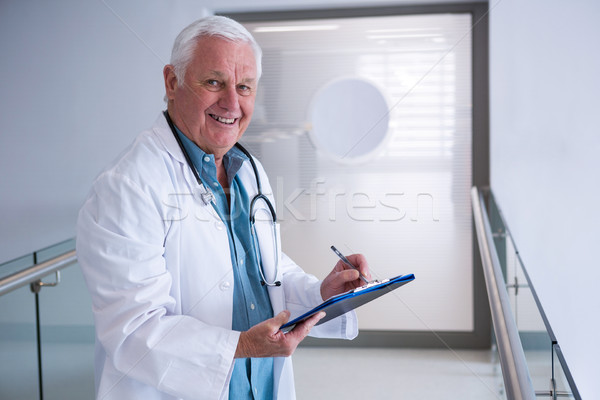Doctor writing on clipboard in the passageway at hospital Stock photo © wavebreak_media