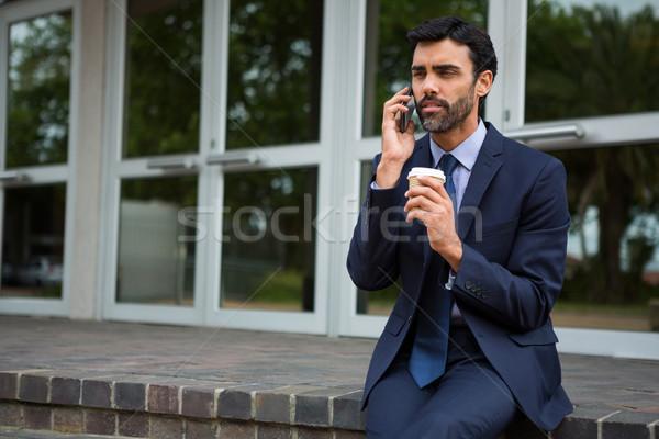 üzletember tart eldobható kávéscsésze beszél mobiltelefon Stock fotó © wavebreak_media