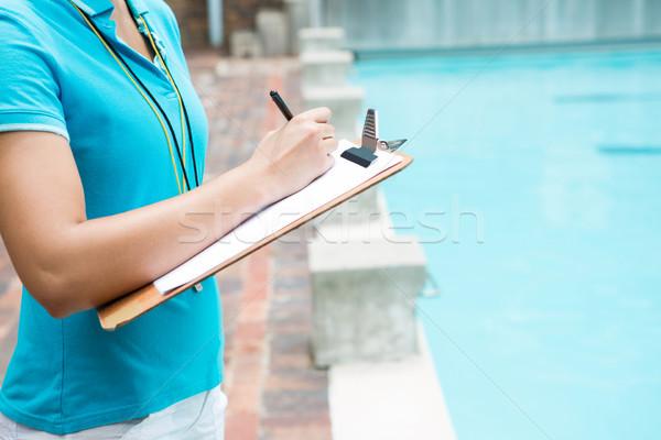 Female coach writing on clipboard near poolside Stock photo © wavebreak_media