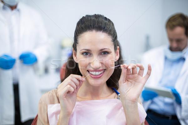Female patient flossing her teeth Stock photo © wavebreak_media