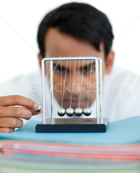 Serious businessman having fun with kinetic balls Stock photo © wavebreak_media