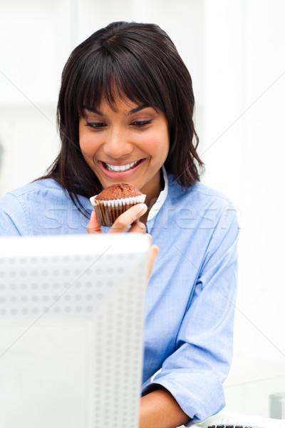Encantador empresária alimentação bolinho secretária feliz Foto stock © wavebreak_media