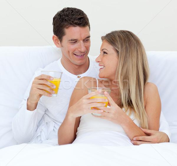 Intimate couple drinking orange juice lying on their bed  Stock photo © wavebreak_media