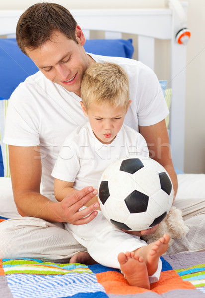 Blond little boy and his father playing with a soccer ball Stock photo © wavebreak_media