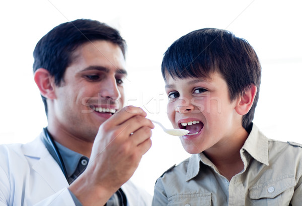 Assertive doctor giving medicine to a little boy Stock photo © wavebreak_media