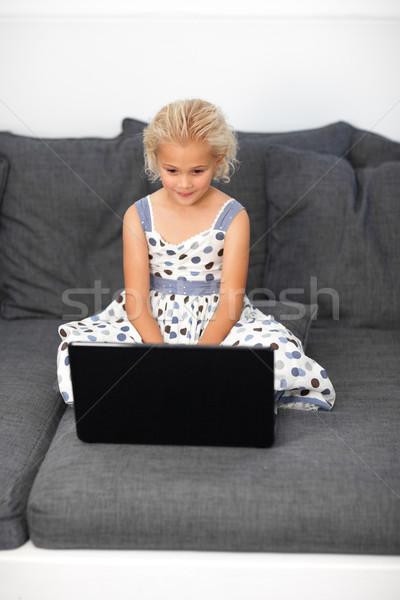 Cute girl using a laptop on a sofa Stock photo © wavebreak_media