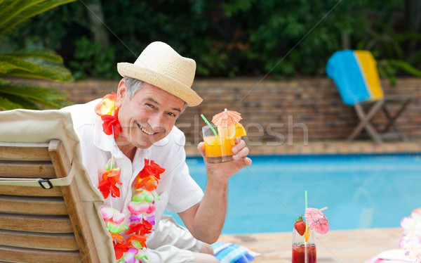 Mature man drinking a cocktail  beside the swimming pool Stock photo © wavebreak_media