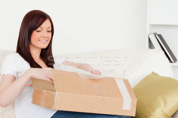 Attractive red-haired woman opening a carboard box while sitting on a sofa in the living room Stock photo © wavebreak_media
