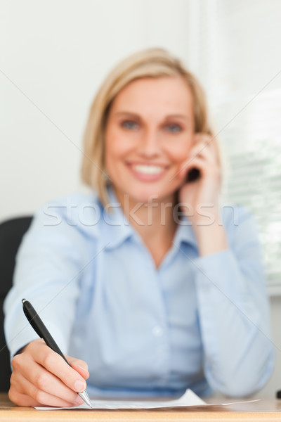 Portrait of a cute businesswoman on mobile noting something looking into camera in her office Stock photo © wavebreak_media