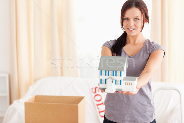 Young woman with a model house looking at the camera in a living room Stock photo © wavebreak_media