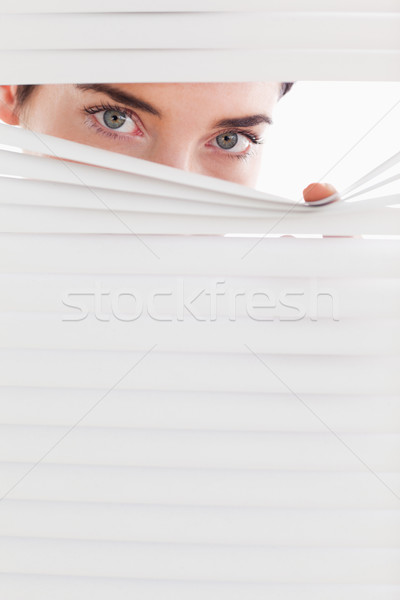Businesswoman peeking through a venetian blind in an office Stock photo © wavebreak_media