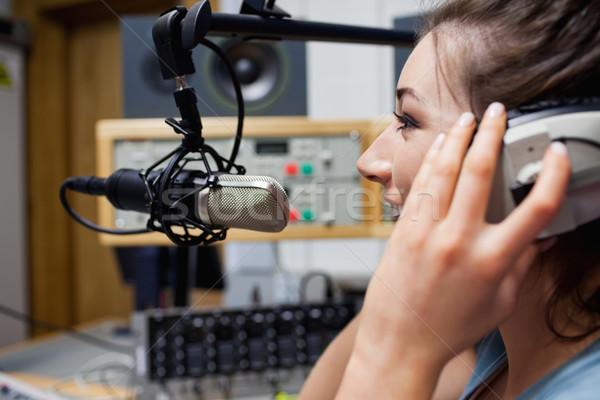 Smiling radio host speaking through a microphone Stock photo © wavebreak_media