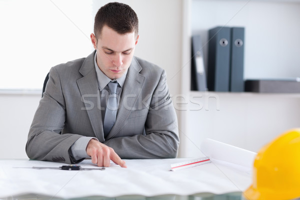 Architect sitting behind a table and checking a building plan Stock photo © wavebreak_media