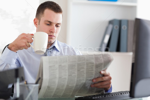 Young businessman having a coffee while reading the newspaper Stock photo © wavebreak_media