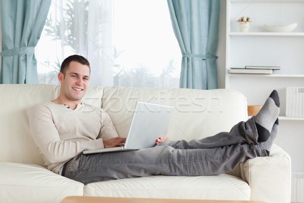 Souriant homme détente portable salon ordinateur Photo stock © wavebreak_media