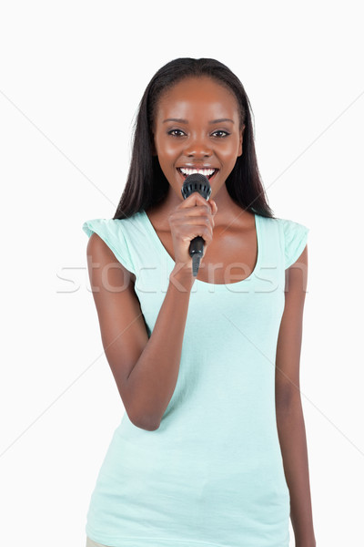 Brightly smiling young female singer against a white background Stock photo © wavebreak_media