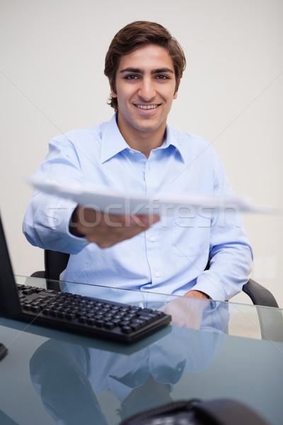 Smiling young businessman handing over paperwork Stock photo © wavebreak_media