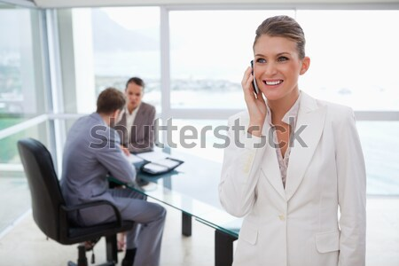 Smiling marketing manager standing in conference room with team sitting behind her Stock photo © wavebreak_media