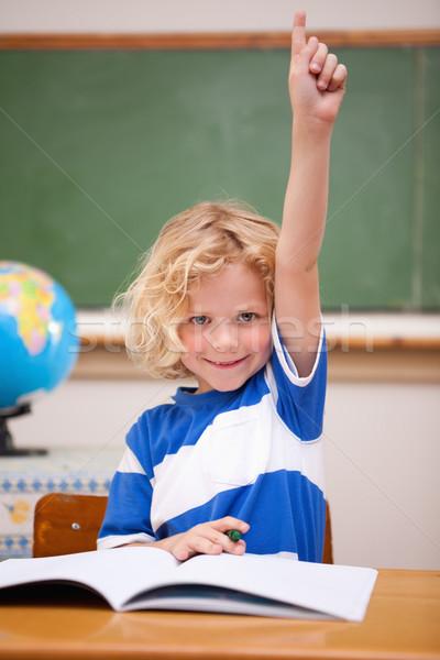 Portrait of a schoolboy raising his hand in a classroom Stock photo © wavebreak_media