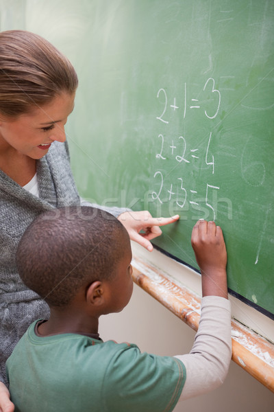 Portrait of a cute teacher and a pupil making an addition on a blackboard Stock photo © wavebreak_media