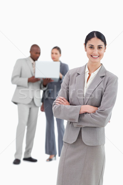 Smiling tradeswoman with folded arms and co-workers behind her against a white background Stock photo © wavebreak_media