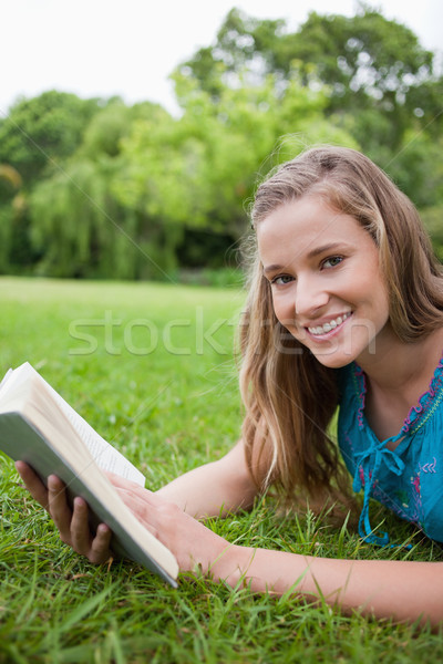 Smiling teenager holding a book while lying in a parkland and looking at the camera Stock photo © wavebreak_media