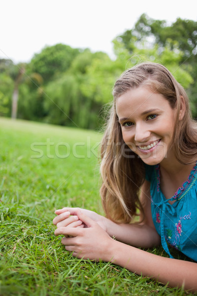 Young attractive woman lying down on the grass in a parkland while smiling Stock photo © wavebreak_media