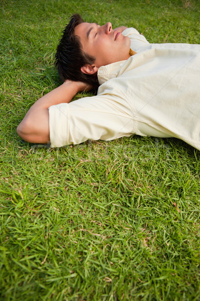 2646897_stock-photo-man-lying-down-in-grass-with-his-eyes-closed-and-both-of-his-hands-resting-behind-his-head.jpg