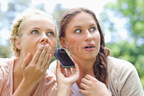 Női barátok hallgat telefonbeszélgetés park telefon Stock fotó © wavebreak_media
