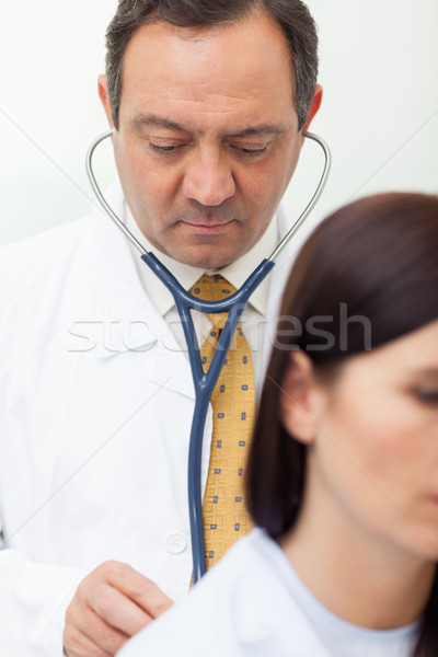 Doctor auscultating a patient in an examination Stock photo © wavebreak_media