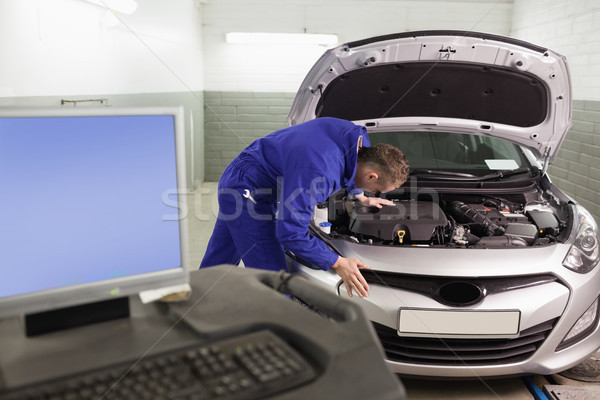 Mechanic repairing a car next to a computer in a garage Stock photo © wavebreak_media