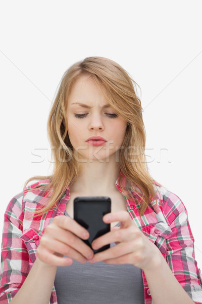 Annoyed woman using a mobile phone against a white background Stock photo © wavebreak_media