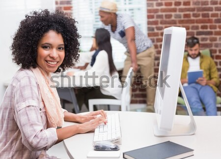 Woman with laptop smiling in data center with man in background Stock photo © wavebreak_media