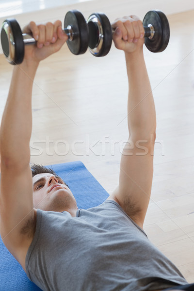 Man lifting  dumbbells while lying on a mat Stock photo © wavebreak_media