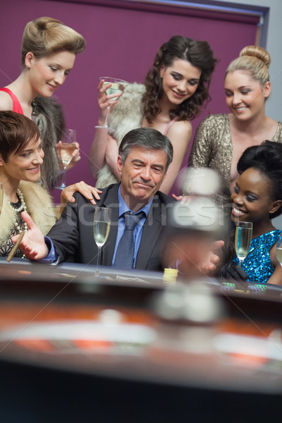 Man surrounded by women accepting of loss in casino Stock photo © wavebreak_media
