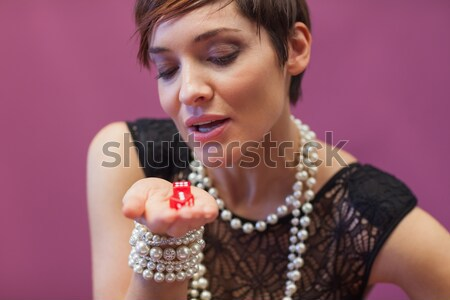 Woman blowing on dice for luck in casino Stock photo © wavebreak_media