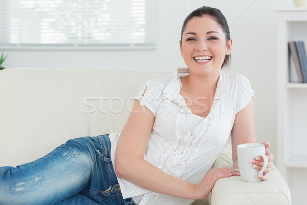 Happy woman holding a mug while lying on the couch in a living room and relaxing Stock photo © wavebreak_media