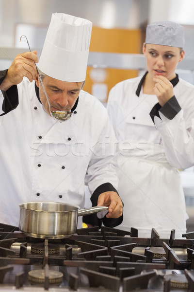 Teacher tasting his students soup with her watching anxiously in kitchen of culinary school Stock photo © wavebreak_media