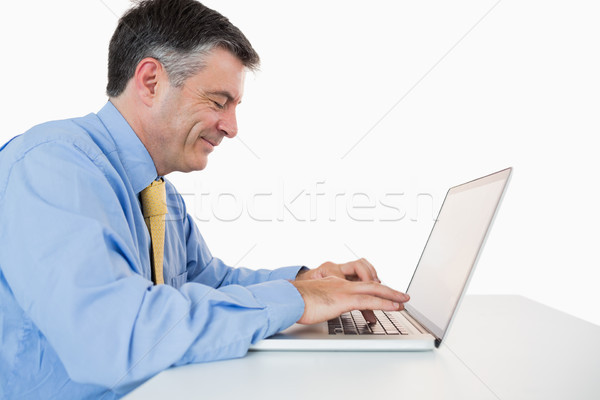 Businessman Smiling And Typing On His Laptop On His Desk In