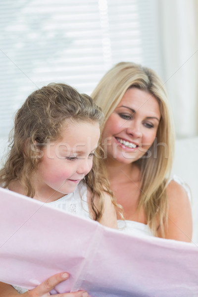 Smiling daughter and mother reading book together in living room Stock photo © wavebreak_media