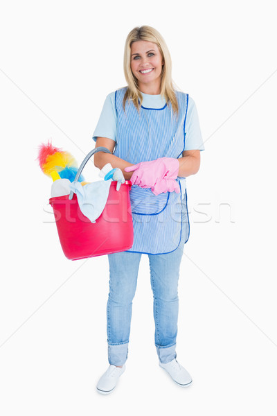 Smiling maid holding a pink bucket in the white background Stock photo © wavebreak_media