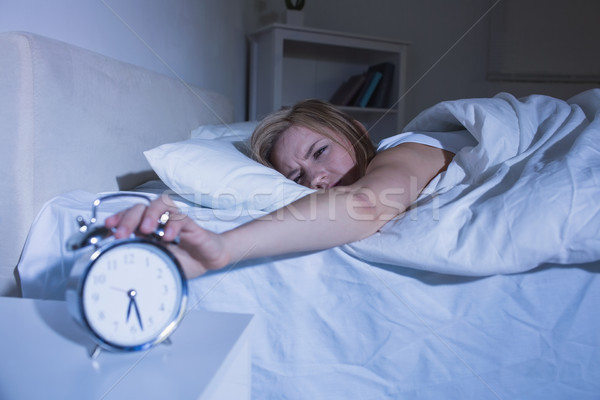 Woman in bed extending hand to alarm clock Stock photo © wavebreak_media