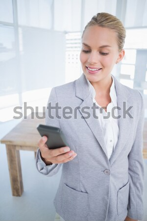 Young business woman text messaging at office desk Stock photo © wavebreak_media