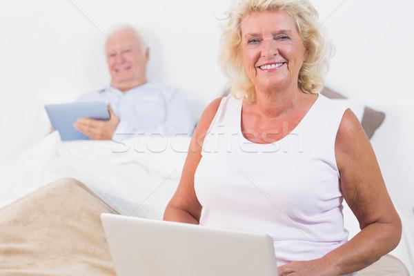 улыбаясь пару таблетка ноутбука спальня Сток-фото © wavebreak_media