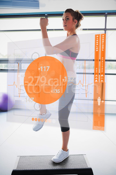 Woman doing exercise with futuristic interface showing calories Stock photo © wavebreak_media