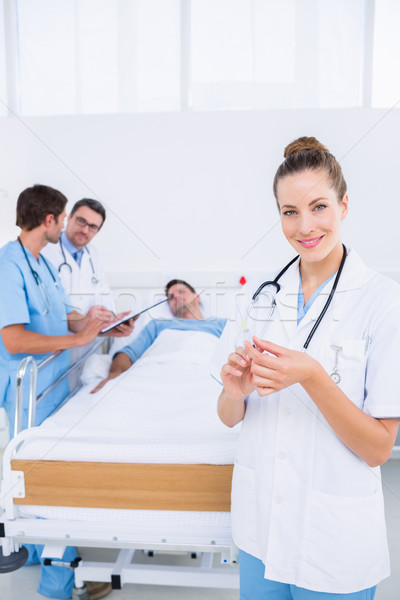 Doctor holding syringe with colleagues and patient in hospital Stock photo © wavebreak_media