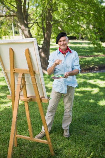 Mature man painting on canvas in park Stock photo © wavebreak_media