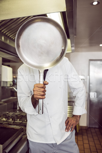 Cook holding pan in front of face in kitchen Stock photo © wavebreak_media