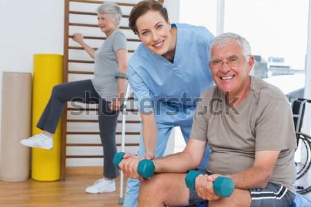 Female therapist assisting senior couple with dumbbells Stock photo © wavebreak_media