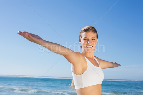 Sporty blonde standing on the beach with arms out Stock photo © wavebreak_media